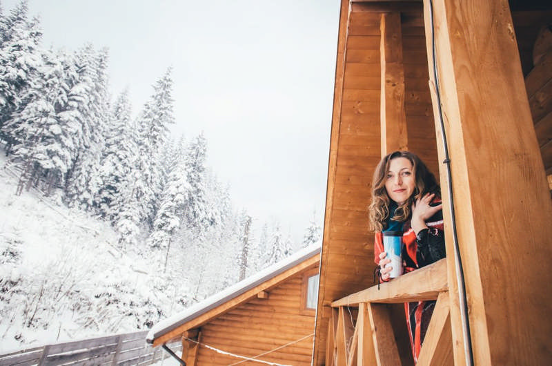 woman enjoying hygge in cabin in winter