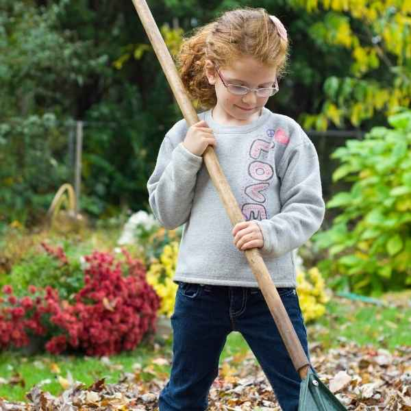 child raking leaves