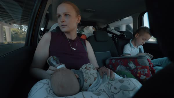 woman sleeping in car with small children