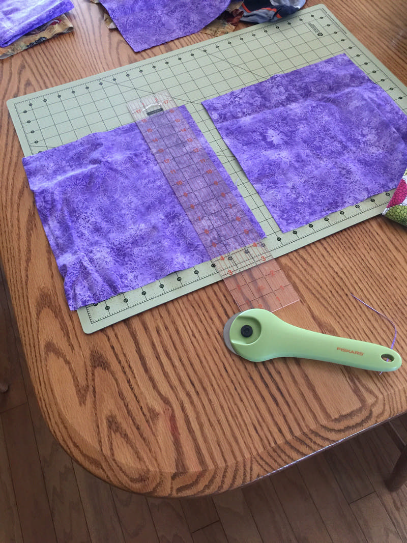 cutting mat with rotary cutter and purple fabric