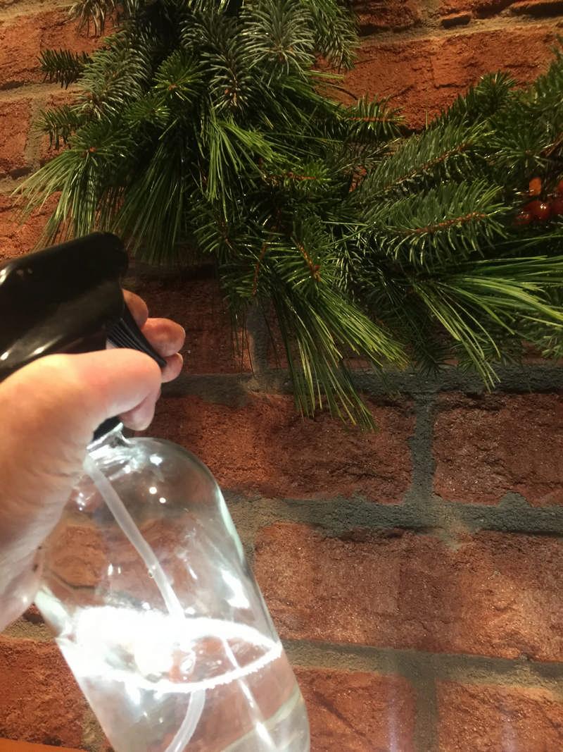 spraying fresh wreath with water