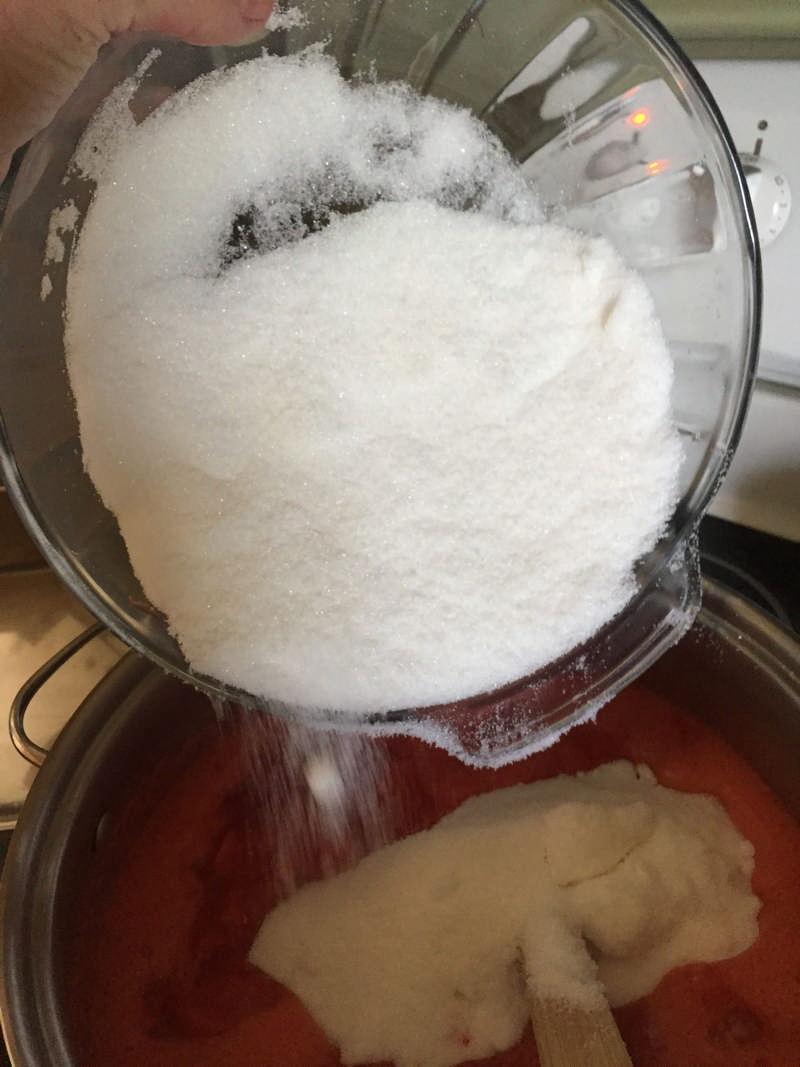 Pouring sugar into preserves