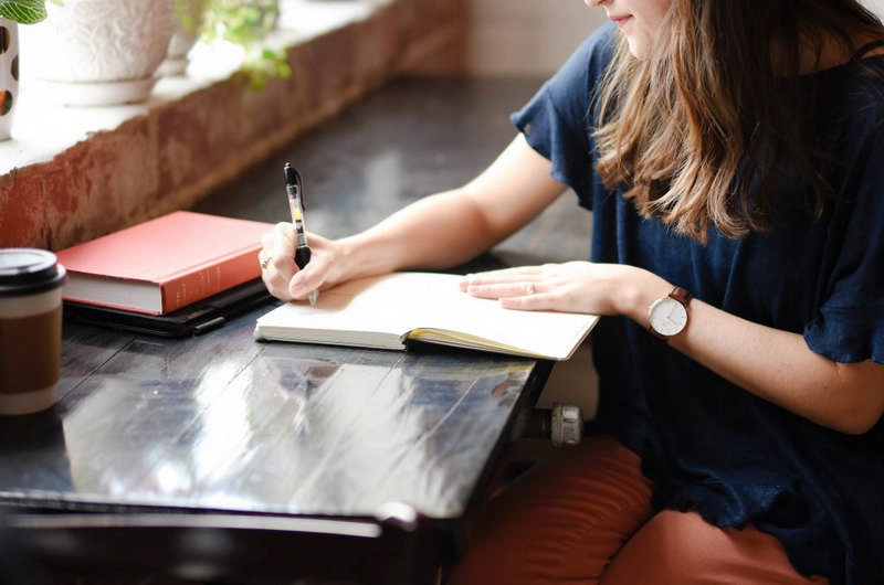 woman writing notes in journal