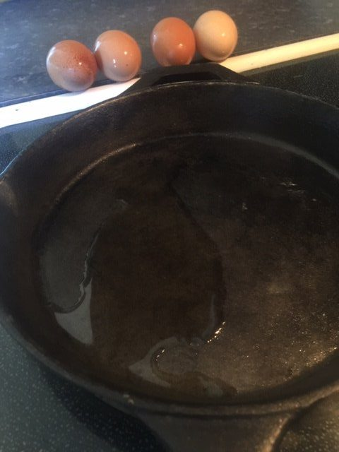 melted ghee in cast iron pan with 4 eggs