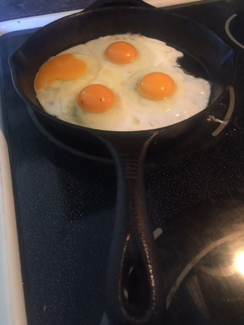 frying 4 eggs in a cast iron pot with ghee