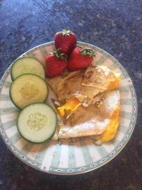 fried eggs, sliced cucumber and strawberries on a plate
