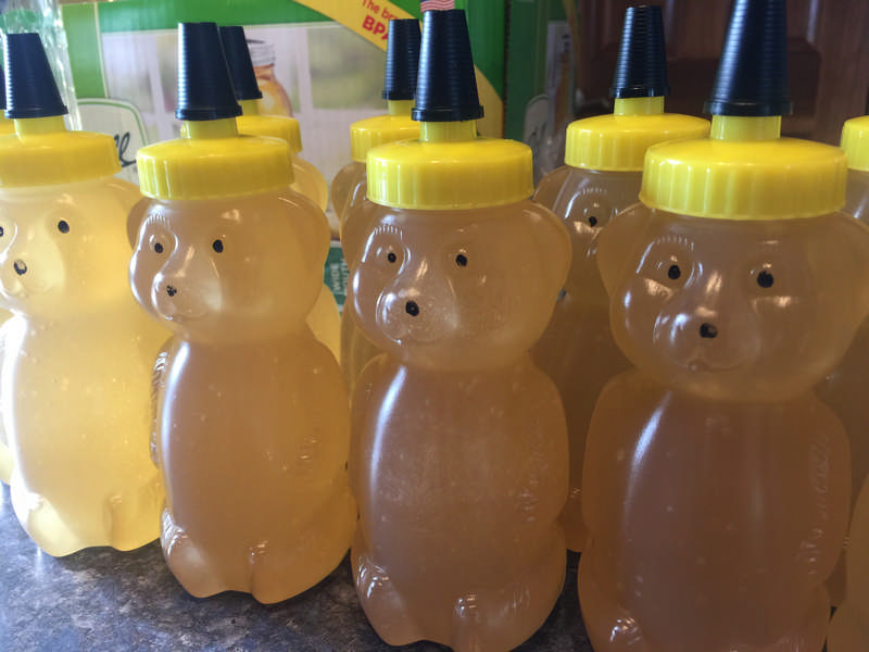 a beekeeper's honey bear bottles with honey