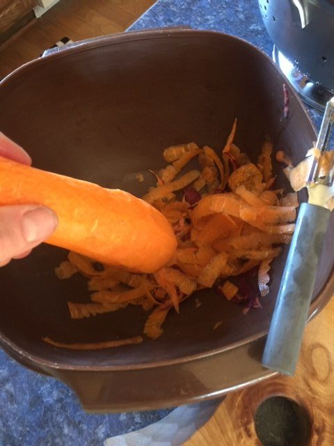 peeling carrots over a bowl