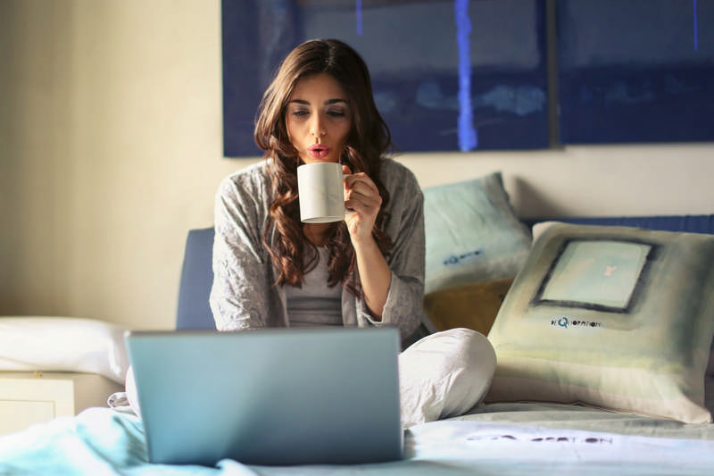 woman drinking coffee and working at home