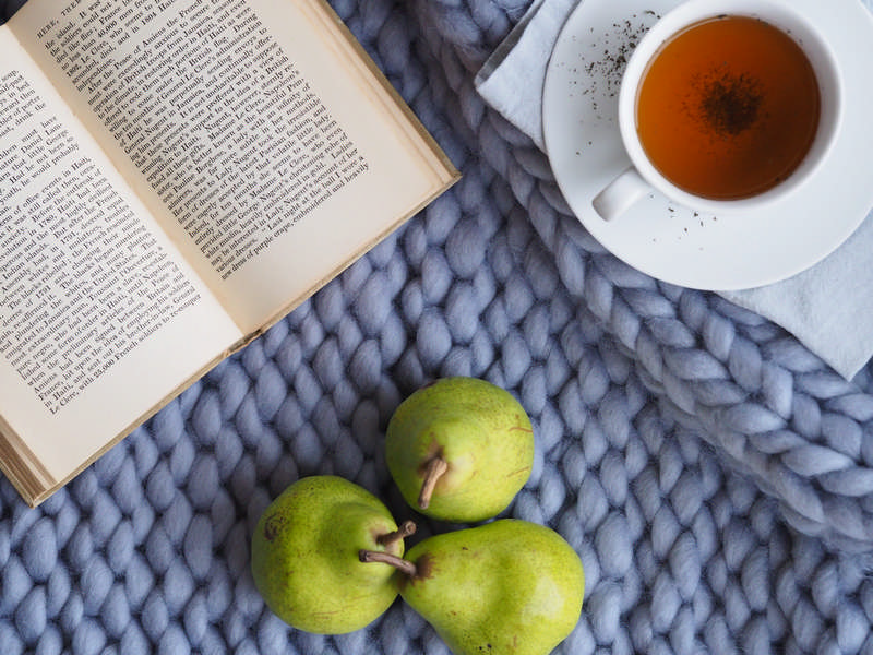 self-care by relaxing with a book and cup of tea with fruit