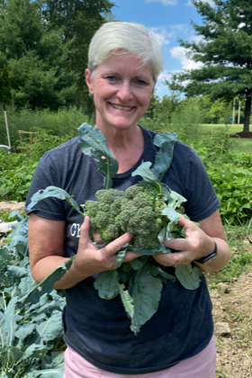 woman holding brocolli in garden