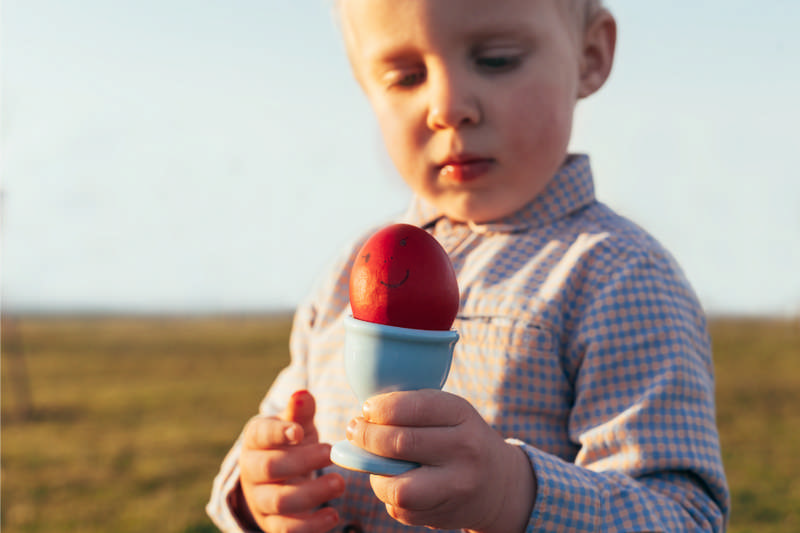 child looking at egg