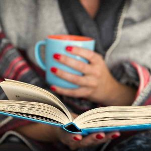 woman reading a book with blanket