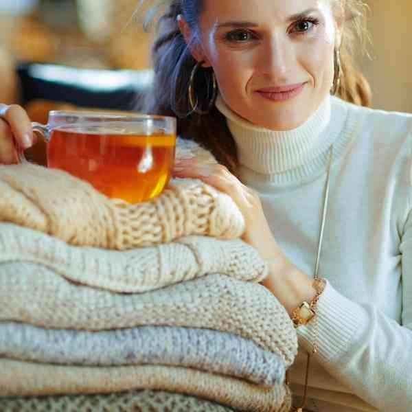 woman with hot tea and stack of sweaters