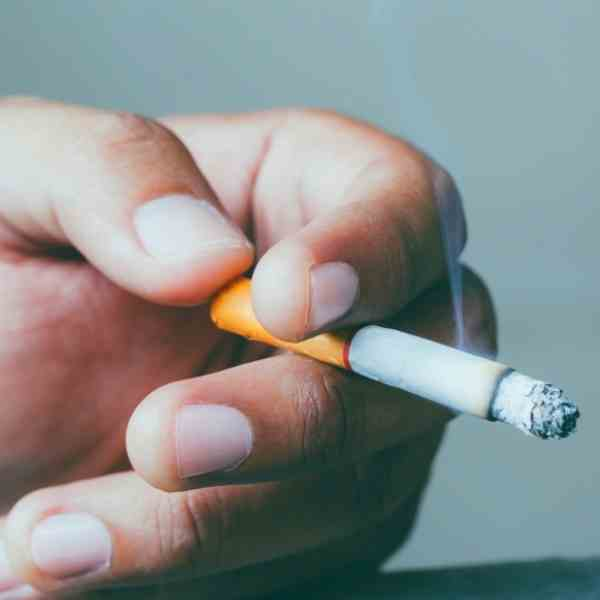 hand holding a lit cigarette